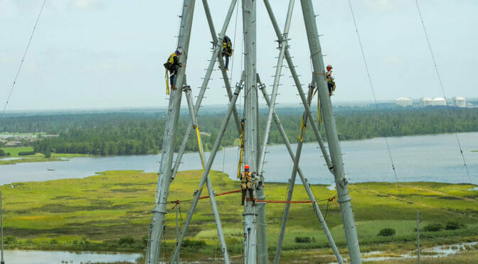 Four workers harnessed up on a telecom tower